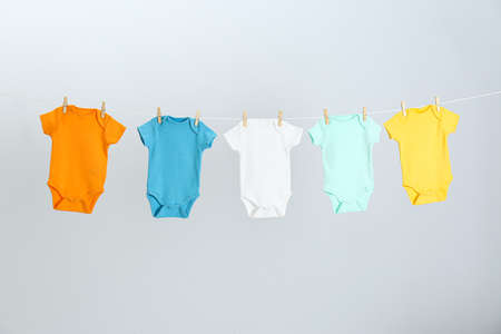 Different baby  clothes hanging on clothes line against light grey background. Laundry day 免版税图像