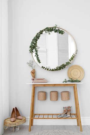 Runder Spiegel und Tisch mit Zubehör in der Nähe der weißen Wand. Modernes Innendesign