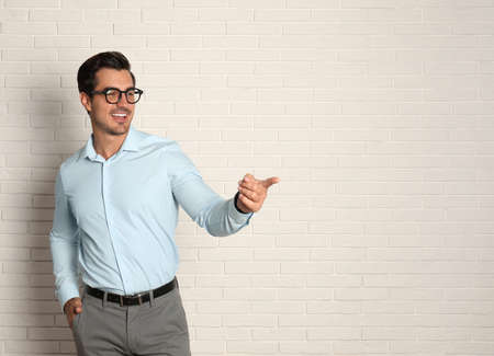 Young male teacher with glasses near brick wall. Space for text