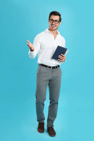 Young male teacher with glasses and notebooks on light blue background Stock Photo