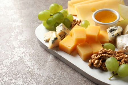 Board with different kinds of delicious cheese and snacks on marble background