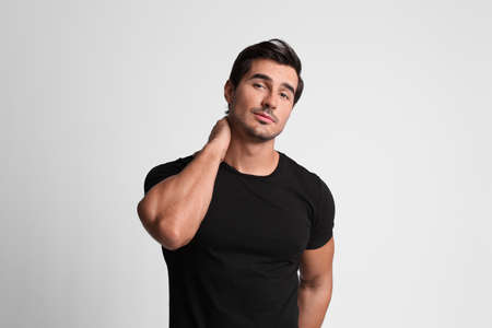Portrait of handsome young man in black t-shirt on grey background Standard-Bild