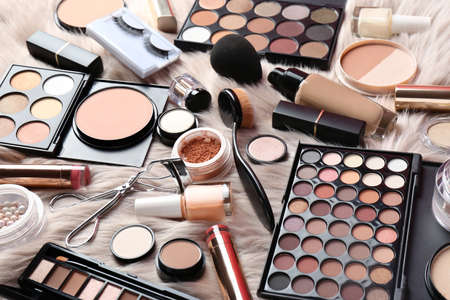Set of different professional makeup products on furry plaid