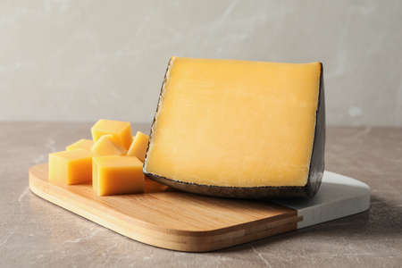 Board with delicious cut cheese on marble table