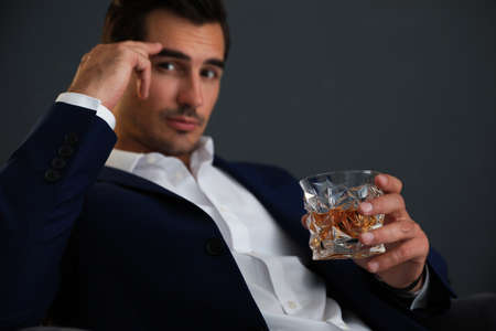 Young man with glass of whiskey on dark background