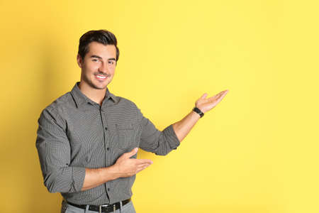 Young male teacher on yellow background. Space for text Foto de archivo