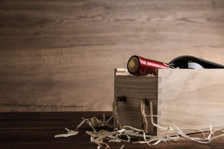 Open wooden crate with bottle of wine on table, space for text