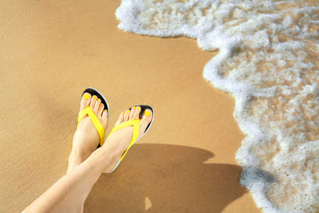 Closeup of woman with flip flops on sand near sea, space for text. Beach accessories