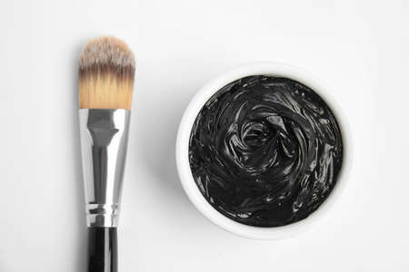 Professional face mask with brush on white background, top view