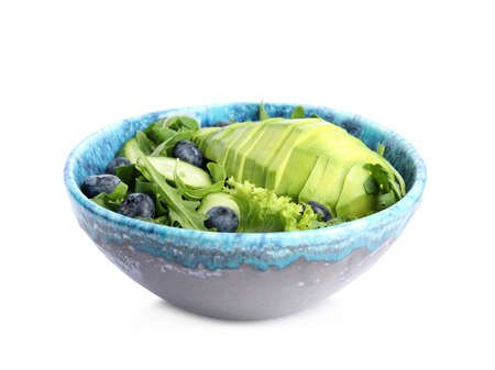 Delicious avocado salad with blueberries in bowl on white background