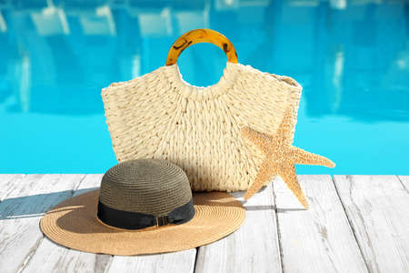 Beach accessories on wooden deck near outdoor swimming pool