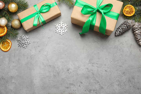 Christmas decoration and gift boxes on light stone background, flat lay. Space for text
