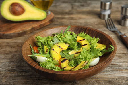 Delicious avocado salad with boiled eggs in bowl on wooden table