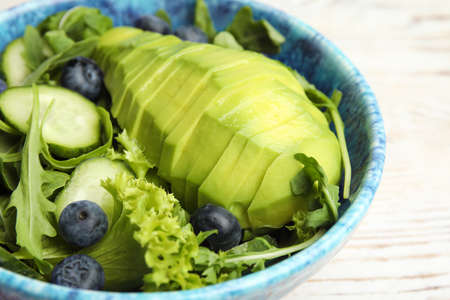 Delicious avocado salad with blueberries in bowl on table, closeup Banco de Imagens