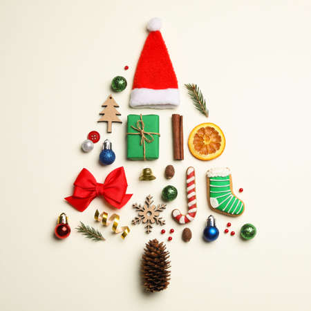 Flat lay composition with Christmas tree made of different holiday items on light background