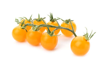 Branch of ripe yellow cherry tomatoes on white background