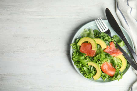 Delicious avocado salad with salmon on white wooden table, flat lay. Space for text