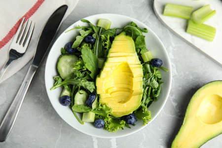 Delicious avocado salad with blueberries in bowl on grey marble table, flat lay
