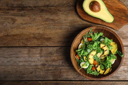 Delicious avocado salad with boiled eggs in bowl on wooden table, flat lay. Space for text