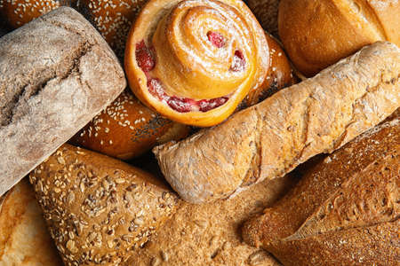 Fresh breads and pastry as background, top view