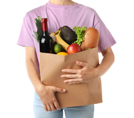 Woman holding shopping paper bag with different groceries on white background