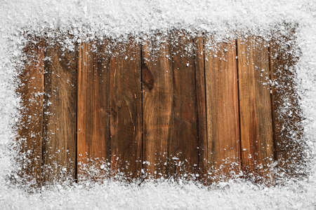 Frame of white snow on wooden background, top view with space for text. Christmas season