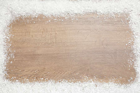 Frame of white snow and space for text on wooden background, top view. Christmas season Imagens