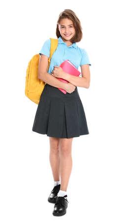 Niña feliz en uniforme escolar sobre fondo blanco. Foto de archivo