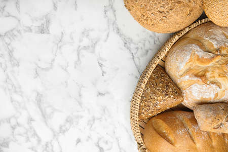 Loaves of different breads on white marble background, flat lay. Space for text
