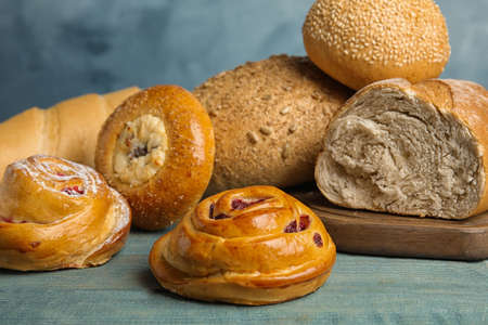 Fresh breads and pastries on blue wooden table