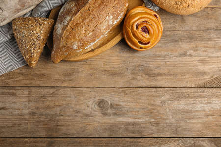 Fresh breads and pastry on wooden background, flat lay. Space for text Imagens