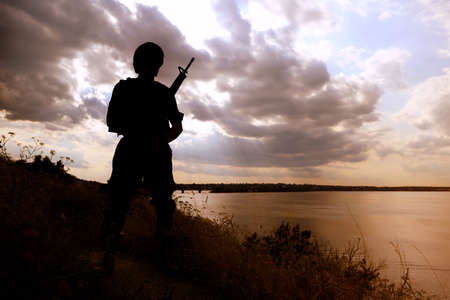 Soldier with machine gun patrolling outdoors. Military service