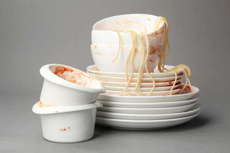Set of dirty dishes with spaghetti leftovers on grey background Stock fotó