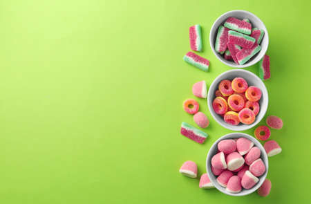 Flat lay composition with bowls of different jelly candies on green background. Space for text