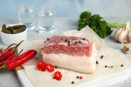 Composition with pork fatback and spices on white table against blue background