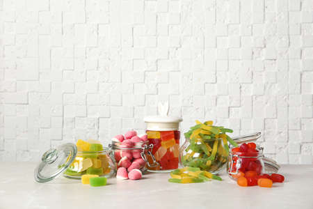 Glass jars with tasty jelly candies on table against white wall, space for text