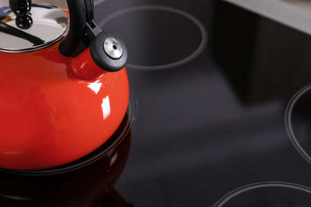 Modern kettle with whistle on stove, closeup. Space for text
