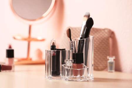 Conjunto de productos cosméticos decorativos para maquillaje en tocador. Espacio para texto Foto de archivo