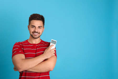 Happy young man with air conditioner remote control on light blue background. Space for text Stockfoto