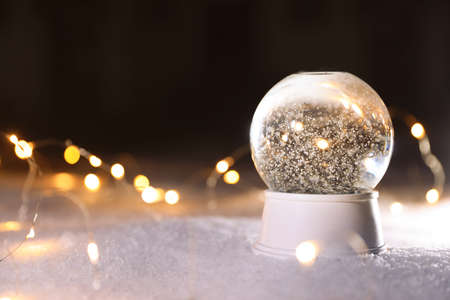 Crystal globe and Christmas lights on white snow outdoors. Space for text