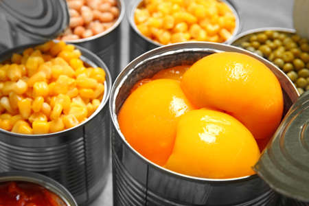 Open tin cans with conserved products, closeup 免版税图像