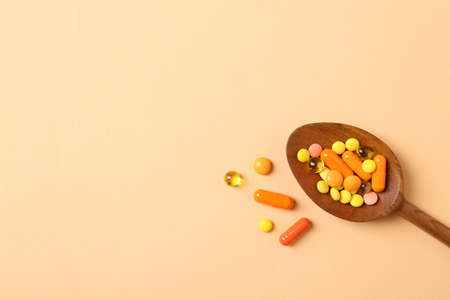 Wooden spoon with different pills and space for text on color background, top view