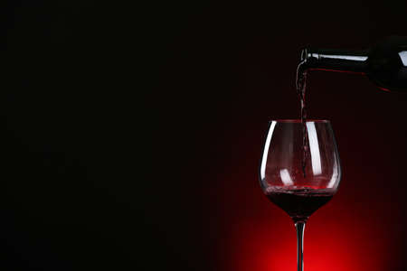 Pouring wine from bottle into glass on dark background, space for text