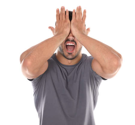 Young man being blinded and covering eyes with hands on white background