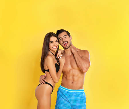 Young attractive couple in beachwear on yellow background