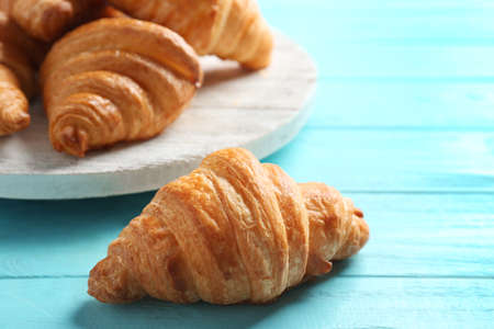 Fresh croissants on light blue wooden table. French pastry