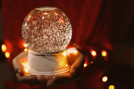 Woman holding snow globe and Christmas lights in darkness, closeup Stockfoto