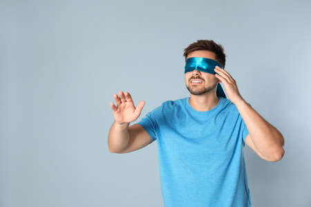 Young man with light blue blindfold on grey background