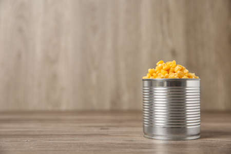 Open tin can of sweet corn on wooden table, space for text