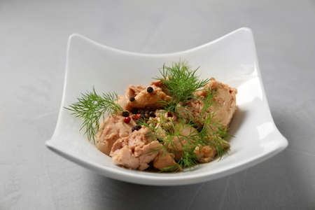 Plate with tasty canned cod liver on grey table